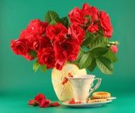Roses rouges et une cuvette de thé Images stock