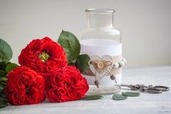 Roses rouges fraîches de jardin de vintage avec un vase ` S de Valentine ou concept de carte postale de jour de ` s de mariage Images libres de droits