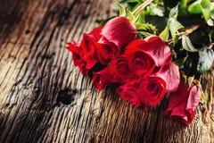 Roses rouges Le bouquet des roses rouges libèrent le mensonge sur la table de chêne rustique Image stock