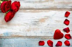 Roses rouges, pétales de rose et coeur sur le fond en bois de vintage Images stock