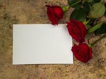 Roses rouges, pétales et papier vide blanc sur un fond en bois Images stock