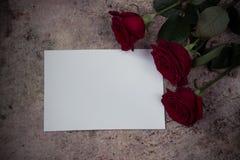 Roses rouges, pétales et papier vide blanc sur un fond en bois Photos stock