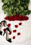 Roses rouges sur la fourrure blanche, les chaussures noires et les pétales de rose, vue supérieure Photos stock
