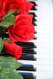 Roses rouges sur un piano Photo stock
