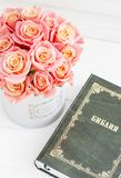 Roses in a round box and the Bible. Beautiful pink roses on a white wooden background. Beautiful pink roses and the Bible. Roses in a Hat Box Stock Photo