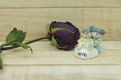 Roses sèches et poupée en céramique sur le fond en bois de modèle Photo stock