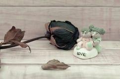 Roses sèches et poupée en céramique sur le fond en bois de modèle avec la couleur Photographie stock