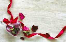 Roses sèches, ruban, boîte transparente de coeur, pétales Photos libres de droits