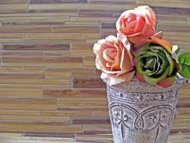 Roses in shabby vase on a bamboo wooden table with copy space royalty free stock image