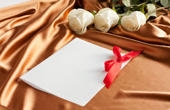 Roses on silk and white card with red bow Stock Photos