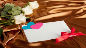 Roses on silk, white cards and a paper heart. Holiday Cards Stock Photos