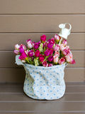 Roses with a small watering pot in fabric vase Stock Photo