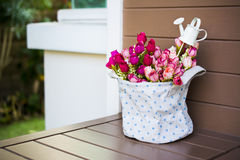 Roses with a small watering pot in fabric vase Royalty Free Stock Photography
