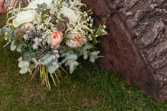 Roses, succulents and other flowers in wedding bouquet on green Royalty Free Stock Photos