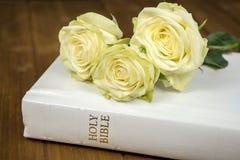 Roses sur la bible blanche Photographie stock