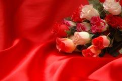 Roses sur le satin rouge Image libre de droits