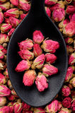 Roses for tea. Top view of black spoon full of roses for tea Royalty Free Stock Photo