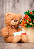 Roses and a teddy bear. On wooden background Royalty Free Stock Photography