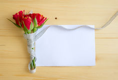 Roses tied with a ribbon lie on the edge of a blank sheet of pap Royalty Free Stock Photography