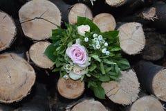 Roses une - le bouquet se trouve entre le bois de chauffage Images stock