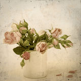 Roses in a vase on a dirty vintage background Stock Images