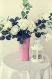 Roses in a vase and lantern. Vase and lamp stand at the round table stock photos
