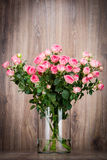 Roses in the vase. On wooden background royalty free stock photography