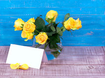 Roses in a vase on wooden background and a postcard for text. Roses in a vase on wooden background and a postcard with space for text Royalty Free Stock Photography