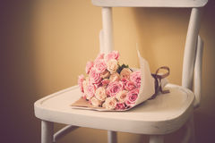 Roses on vintage chair Stock Photos