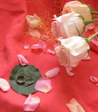 Roses and wedding rings. On a pink fabric showered petals of roses. On one green leaf wedding rings lay. Sideways three light pink roses. Very romantically Stock Photo