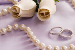 Roses and wedding rings. Over satin Royalty Free Stock Image