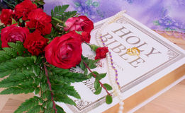 Roses and Wedding Rings. Roses With Bible and Wedding Rings on Wood Table Royalty Free Stock Photos