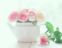 Roses in a white enameled vintage teapot Royalty Free Stock Photo