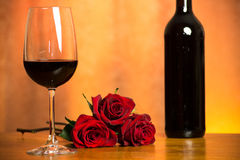 Roses and wine. Red roses along with a glass of wine Royalty Free Stock Images