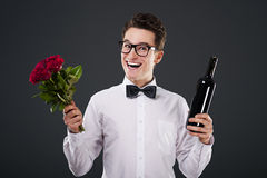 Roses and wine for you. Happy man with a bouquet of roses and wine Royalty Free Stock Images