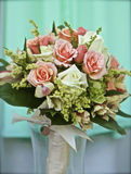 Roses and Wrappings. An elegant bouquet of ivory and pink roses,wrapped in white ribbon against a chartreuse backdrop Royalty Free Stock Photography