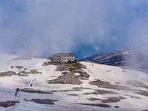 Rosetta mountain hut in a day with snow and fog, Dolomites, Italy. The Rosetta mountain hut in thw snow with lots of hikers around in a day with fog and blue sky Royalty Free Stock Photo