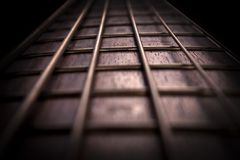 Rosewood bass guitar fret board and strings. With bright backlight closeup stock photography