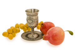 Rosh ha shana.Cup, pomegranates and dates. Silver cup for wine with red pomegranates and yellow dates Royalty Free Stock Photo