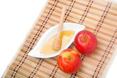 Rosh Ha Shana snack. Apples and honey - a Jewish New Year celebration snack - on a straw mat Royalty Free Stock Photos