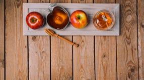 Rosh Hashana假日背景用蜂蜜和苹果在木桌上 在视图之上 免版税库存照片