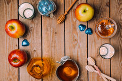 Rosh Hashana holiday background with honey, apples and candles on wooden table. View from above. Stock Images