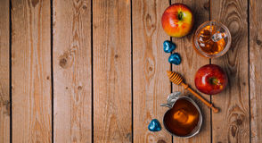 Rosh Hashana holiday background with honey, apples and chocolate on wooden table. View from above. stock image