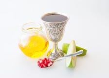 Rosh hashana Kiddush杯子蜂蜜石榴和苹果 免版税图库摄影