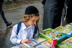 Rosh Hashanah, εβραϊκό νέο έτος 5777 Εορταστικό εμπόριο οδών Ένα παιδί Hasid με τα μακριά payos επιλέγει ένα βιβλίο στοκ εικόνα