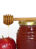 Rosh Hashanah. Jar of honey, honey dipper stick and a red apple - symbols of the Jewish holiday of Rosh Hashanah isolated on white background Stock Photo