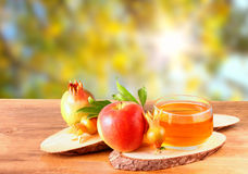 Rosh hashanah concept - apple honey and pomegranate over wooden table. Royalty Free Stock Photography