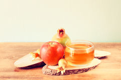 Rosh hashanah concept - apple honey and pomegranate over wooden table. Stock Image