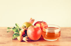 Rosh hashanah concept - apple honey and pomegranate over wooden table. Royalty Free Stock Images