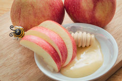 Rosh hashanah. Honey in the plate on wooden background and ripe red apples next is ladles Stock Photography